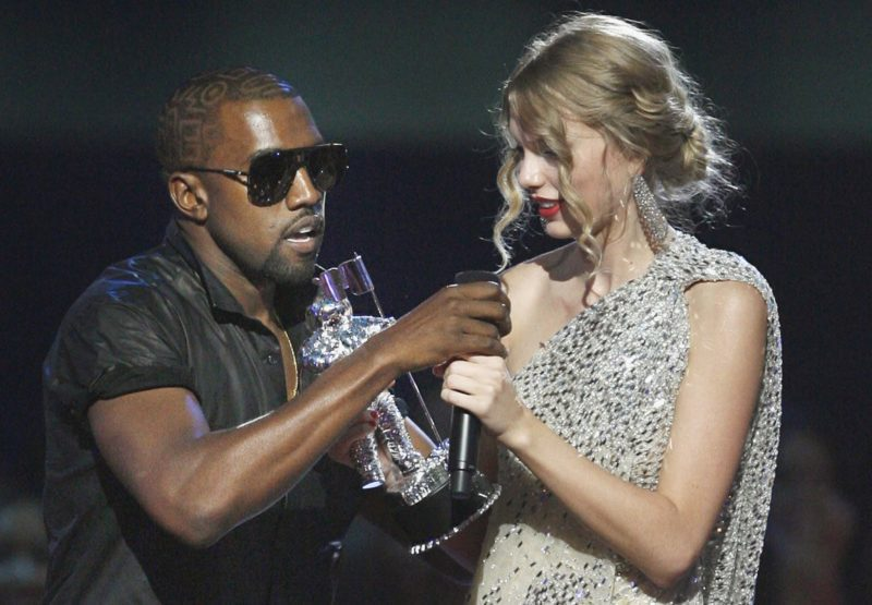 """Singer Kanye West takes the microphone from singer Taylor Swift as she accepts the """"Best Female Video"""" award during the MTV Video Music Awards on Sunday, Sept. 13, 2009 in New York.  (AP Photo/Jason DeCrow)"""