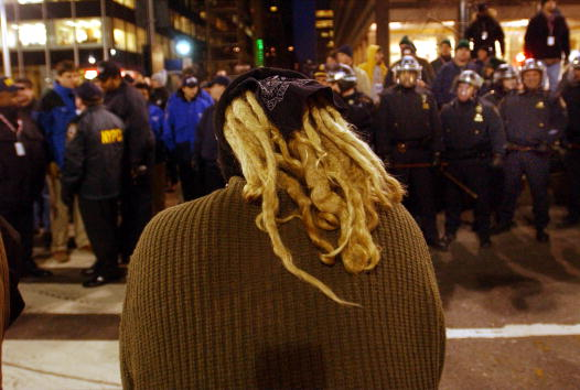 400492 02: An opponent of the World Economic Forum (WEF) stares at police while participating in a anti-WEF march February 2, 2002 in New York City. Thousands of protesters and activists from around the country have descended on New York to rally against the World Economic Forum, a five-day-event in which business and political leaders discuss world economic issues. (Photo by Spencer Platt/Getty Images)