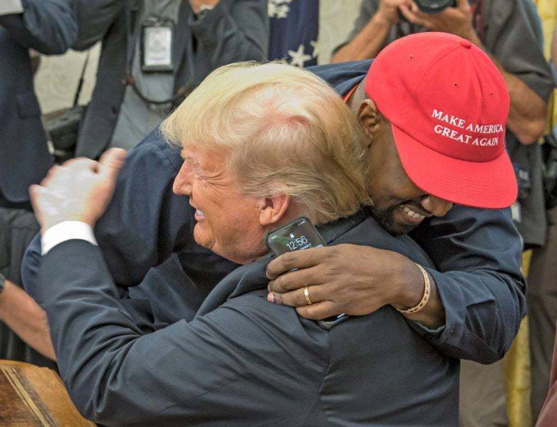 American rapper and producer Kanye West embraces real estate developer and US President Donald Trump in the White House's Oval Office, Washington DC, October 11, 2018. West wears a red baseball cap that reads 'Make America Great Again,' Trump's campaign slogan. (Photo by Ron Sachs/Consolidated News Pictures/Getty Images)